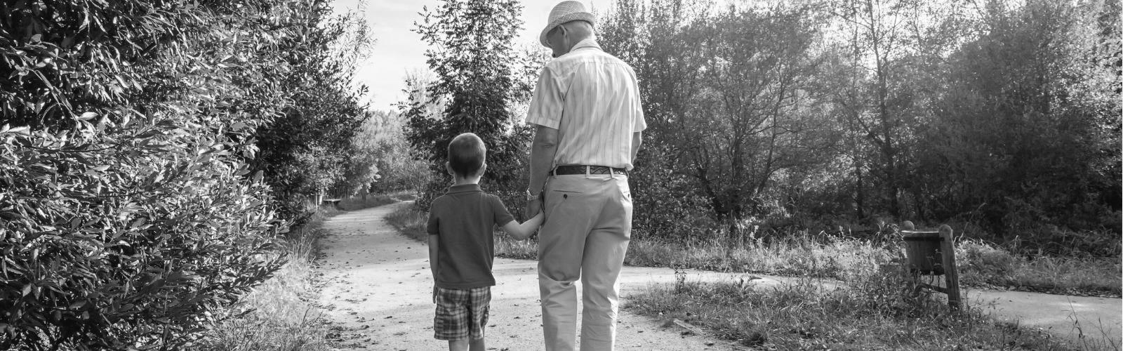 elderly man walking with grandson